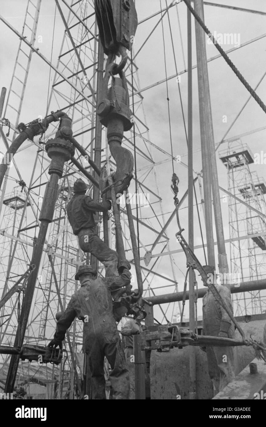Activity at oil well; man on lengths of traveling block will be pulled up to the crown block at top of derrick, - Stock Image