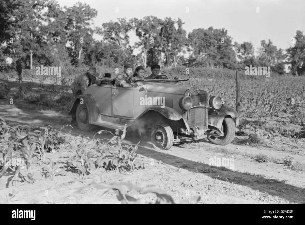 Pushing a car belonging to agricultural day laborer to start it, near Muskogee, Muskogee County, Oklahoma. Date Stock Photo