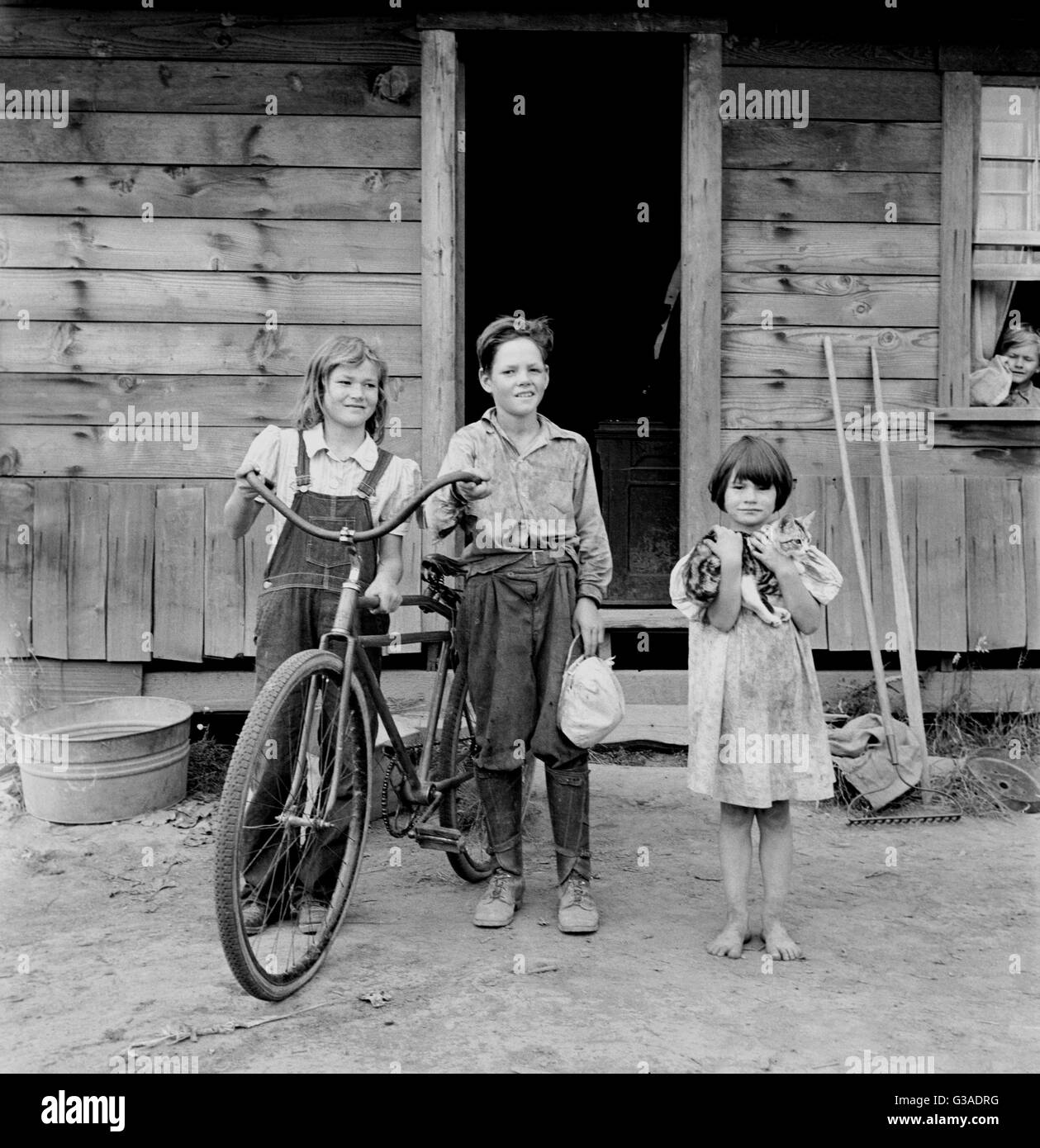 Three of the four Arnold children. The oldest boy earned the money to buy his bicycle. Western Washington, Thurston Stock Photo