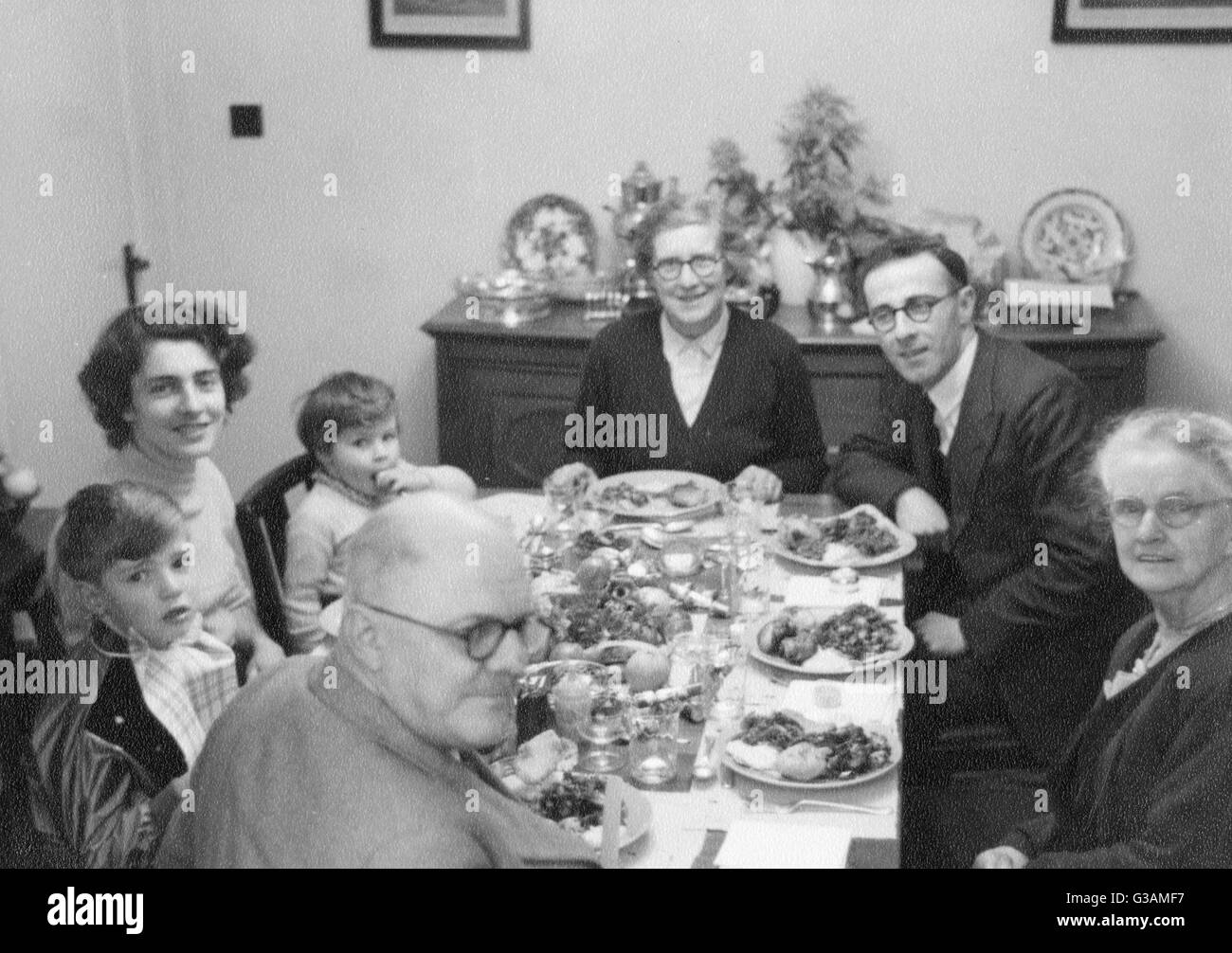 Extended family eating Christmas Dinner. Three generations celebrate with turkey and all the trimmings which rationing Stock Photo