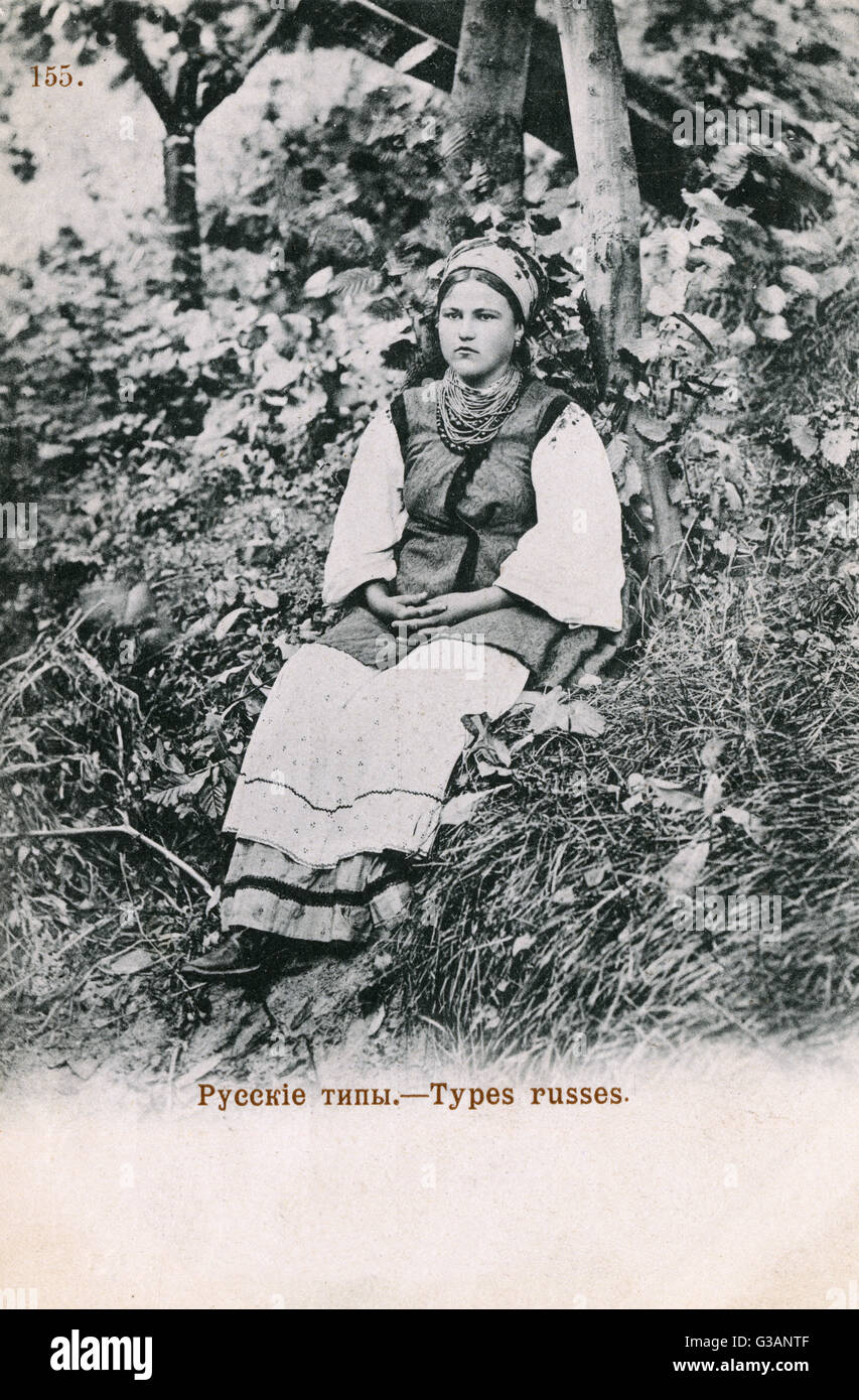 Sullen Russian country girl (in need of a good joke) seated in the undergrowth.     Date: circa 1902 - Stock Image