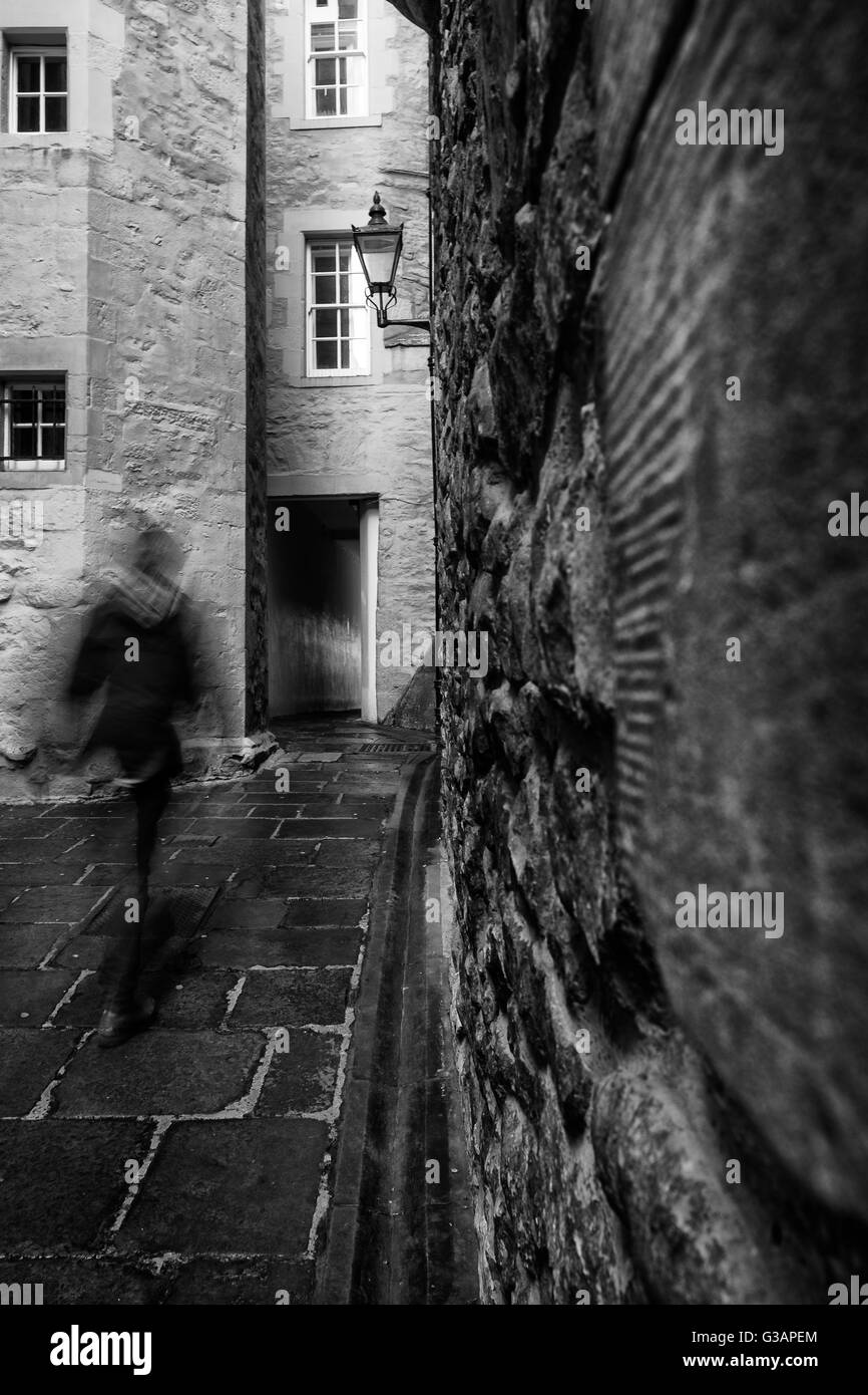 Motion blur as a man walks through one of the many narrow closes (lane) off the Royal Mile in Edinburgh, Scotland - Stock Image