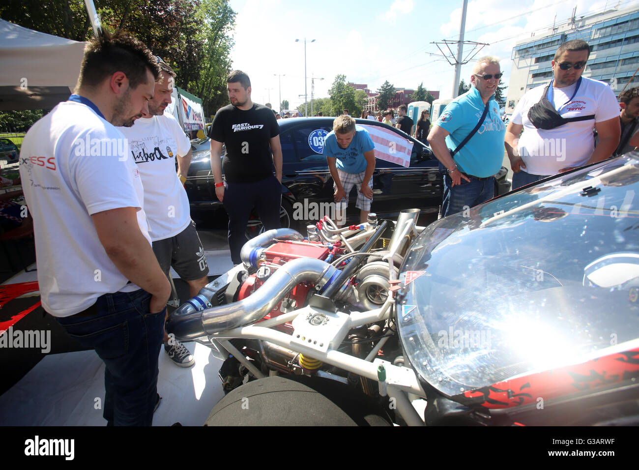 People sightseeing engine on a parked car at Fast and furious street race at Avenue Dubrovnik in Zagreb, Croatia. - Stock Image