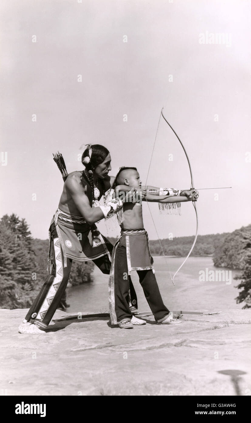young native american indian boy learning to shoot his bow