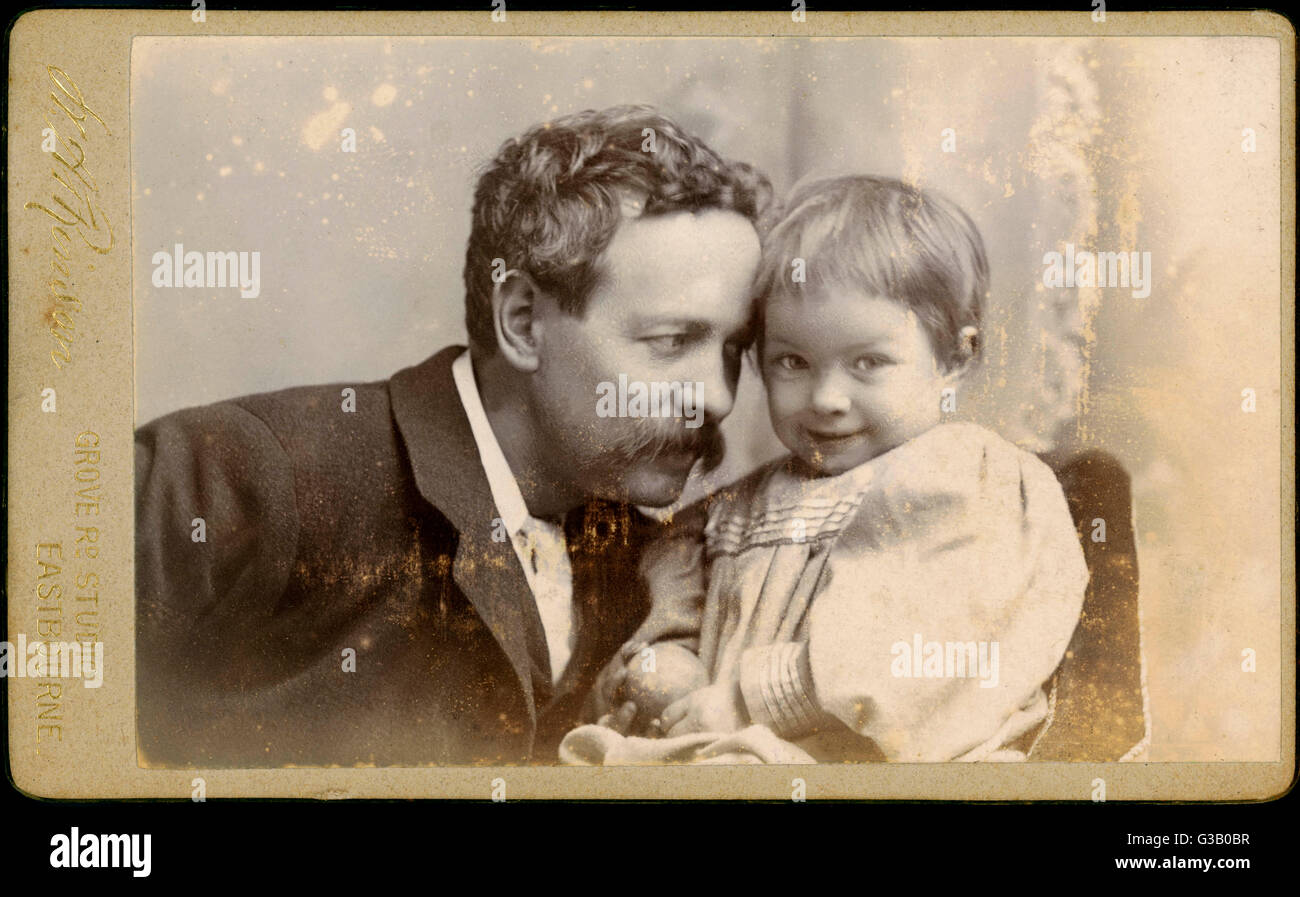 Informally posed portrait of a father and son; their heads  resting against one another.   The son, holding a ball, - Stock Image