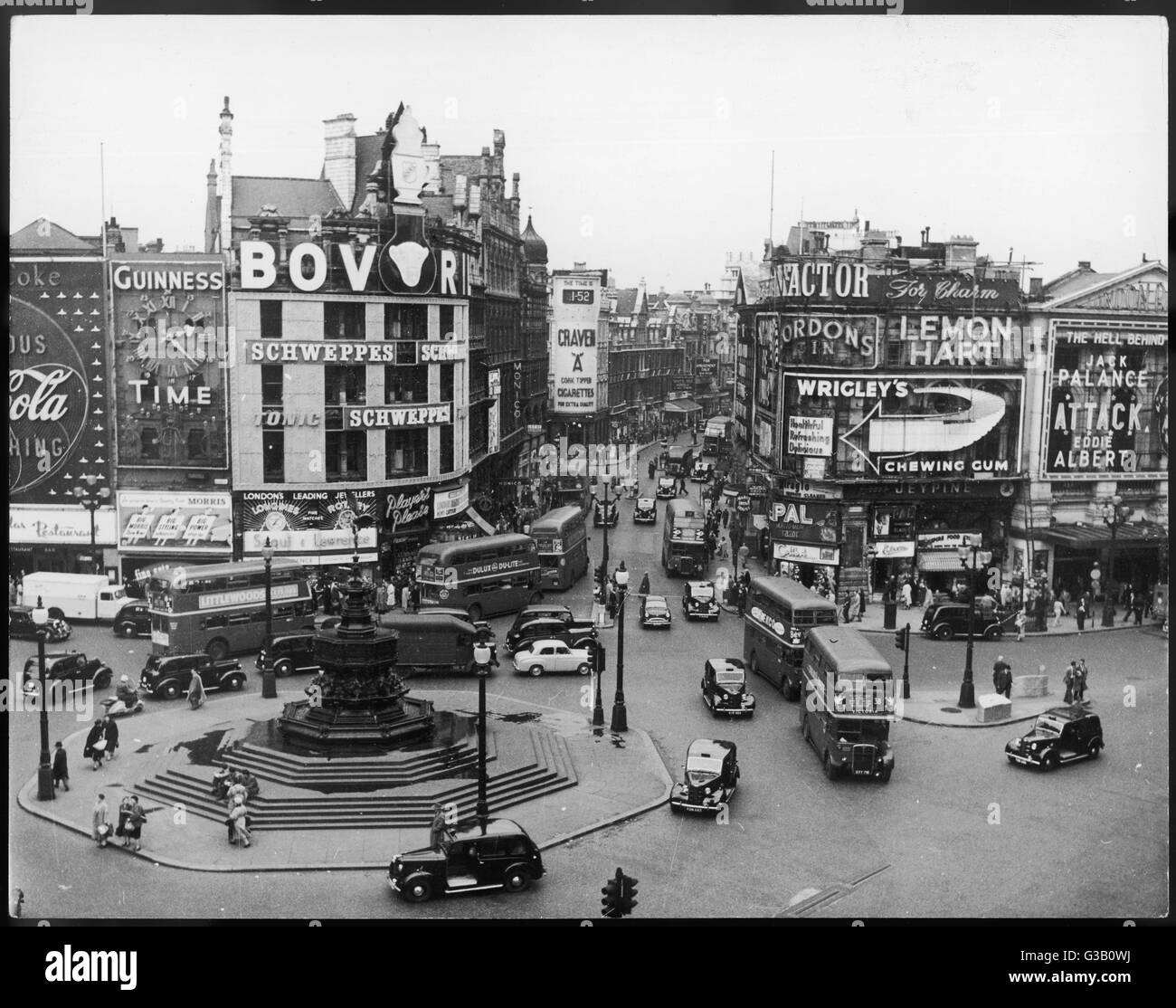 Piccadilly Circus street  scene, with huge billboards advertising Bovril, Wrigley's and Craven A cigarettes - Stock Image