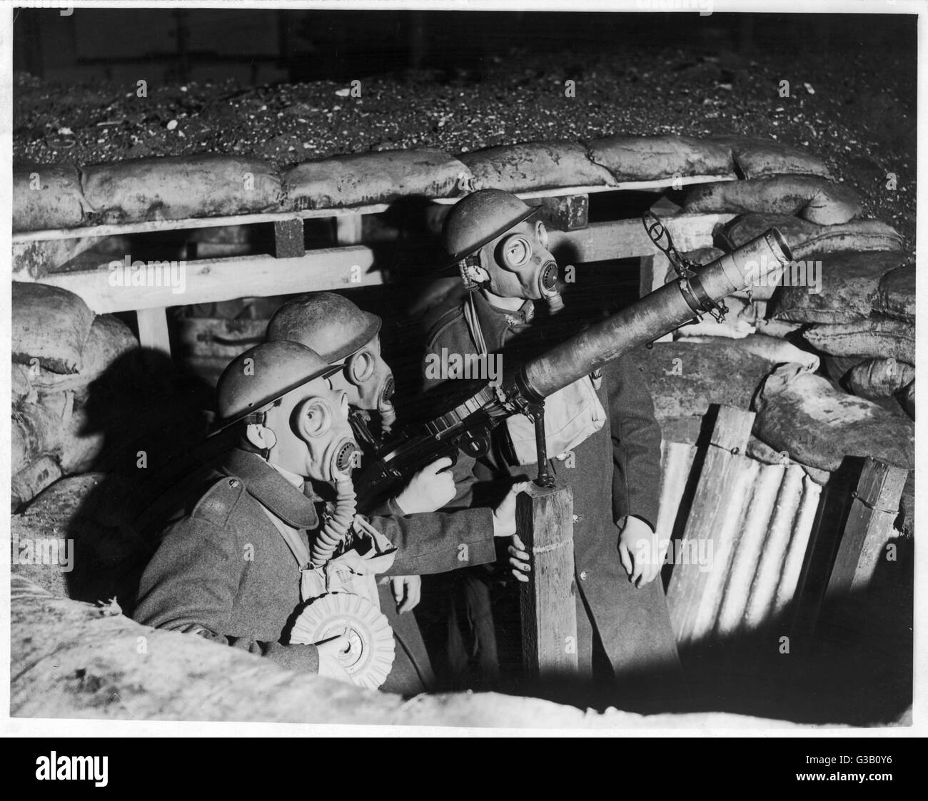 Three soldiers in a pit  wearing gas masks, with  an anti-aircraft Lewis gun.       Date: circa 1940 - Stock Image