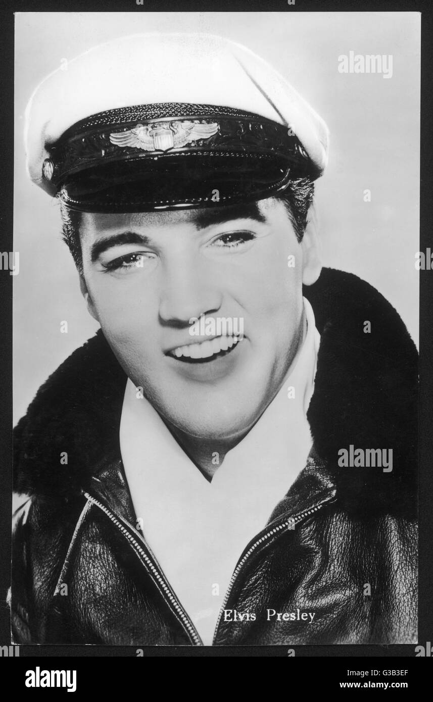 ELVIS PRESLEY  American pop singer, guitarist  and actor in musical films,  seen here in a leather jacket and peaked - Stock Image