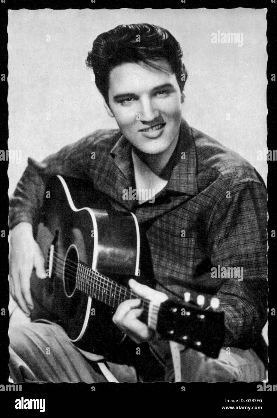 ELVIS PRESLEY  American pop singer, guitarist  and actor in musical films,  seen here with his guitar      Date: - Stock Image