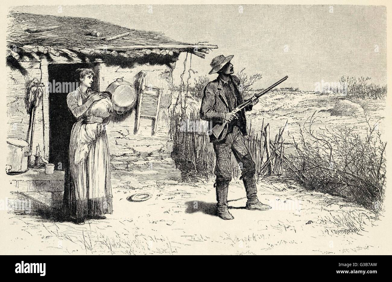 A settler stands ready with a gun outside his shack, with tin bath ...