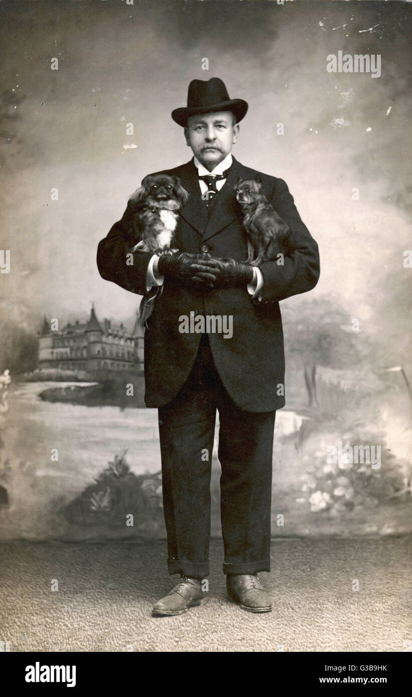 Studio portrait, a man in a black suit with a Pekingese dog under each arm.         Date: circa 1915 - Stock Image