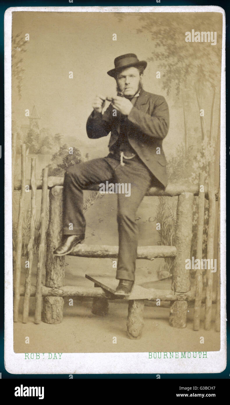 A pipe-smoking man poses on  a stile in the photographer's studio.       Date: circa 1870 - Stock Image