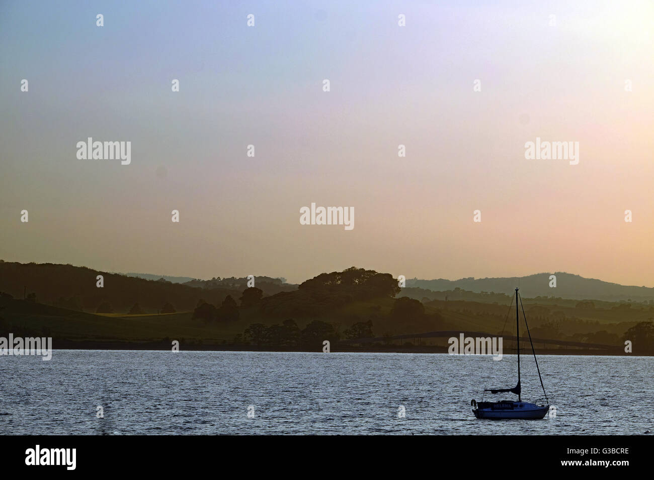 Sunset over the River Exe, with a single sailing boat in silhouette - Stock Image