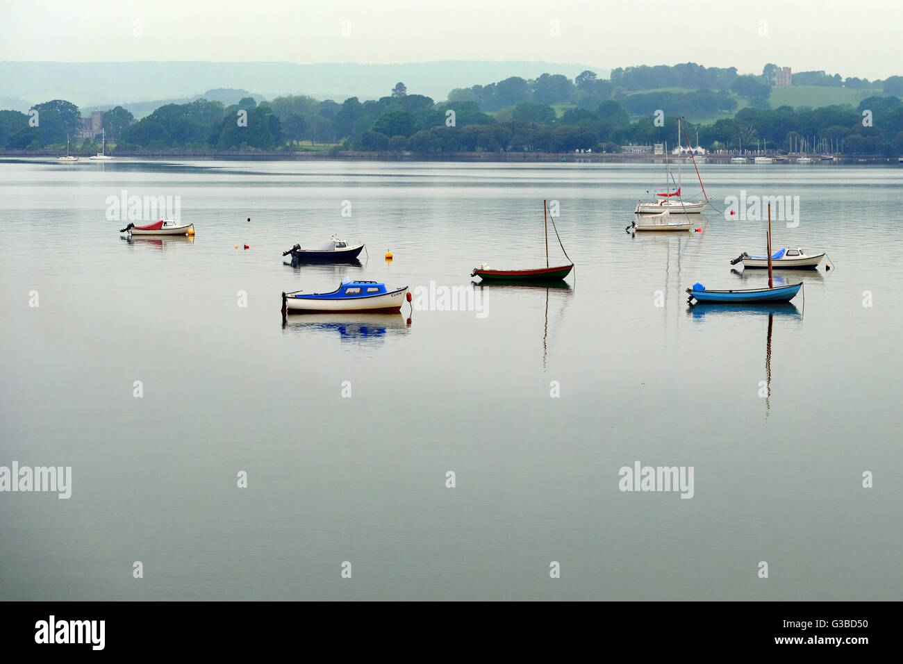 A calm River Exe, with several colourful sailing boats, and Powderham Castle in the distance. - Stock Image