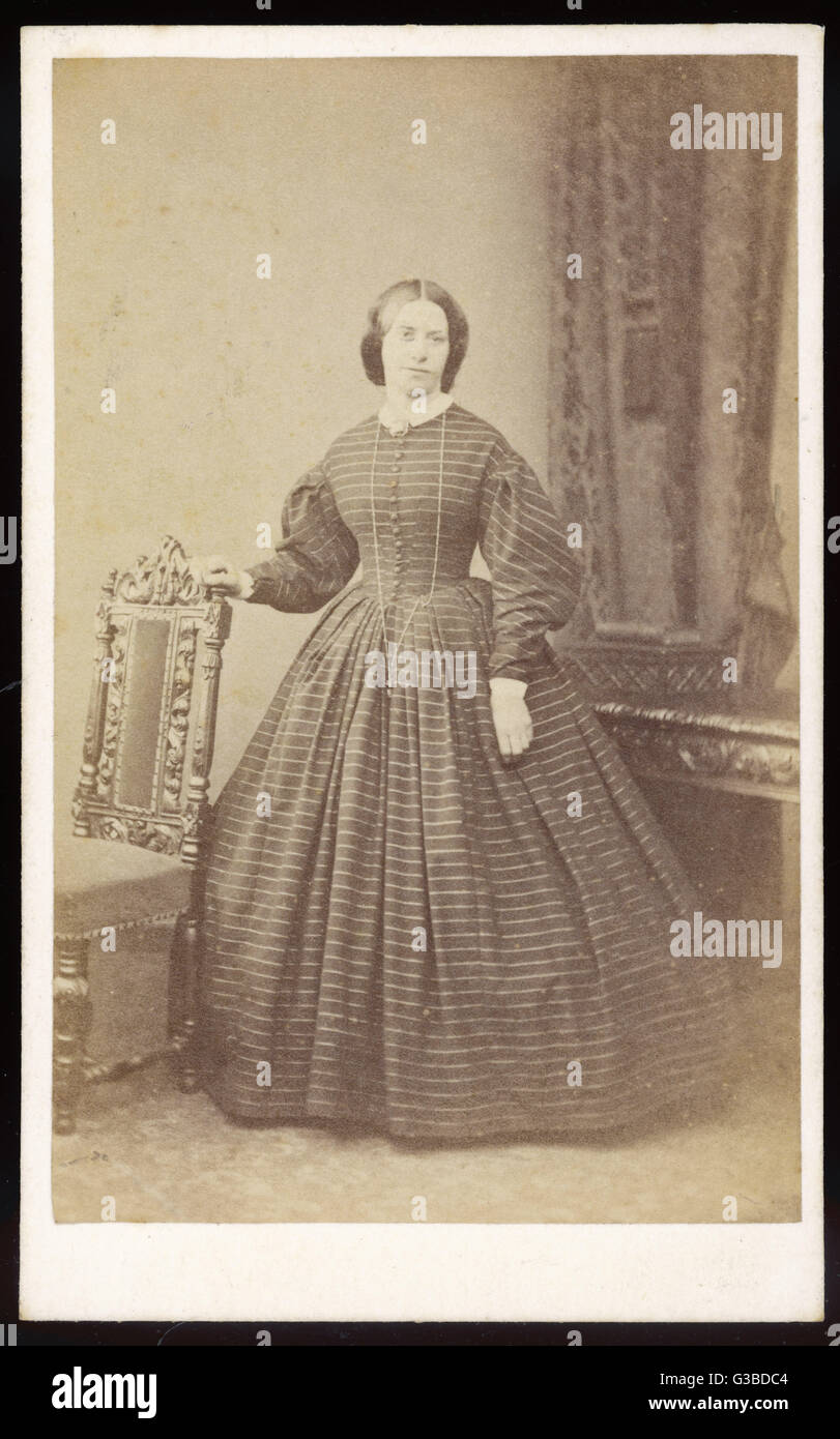A dress in a horizontally  striped fabric with front  buttoning bodice, gigot  sleeves, white cuffs & collar, - Stock Image