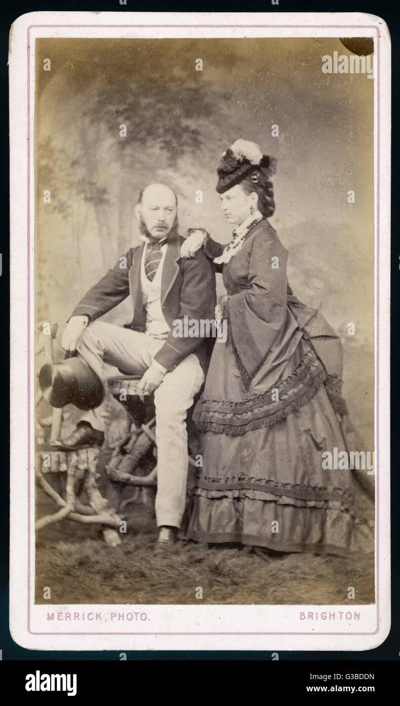 Woman: polonaise with pagoda  sleeves, coils of false hair &  a tiny hat tilted forwards.  Man: light coloured - Stock Image