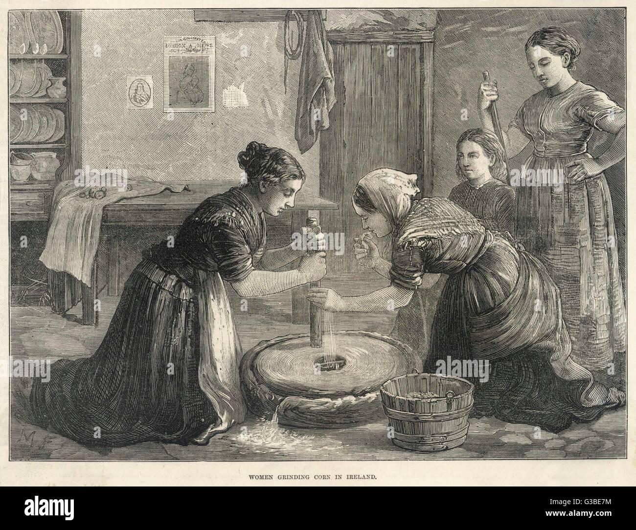 Irish women grind corn by  hand.         Date: 1874 - Stock Image