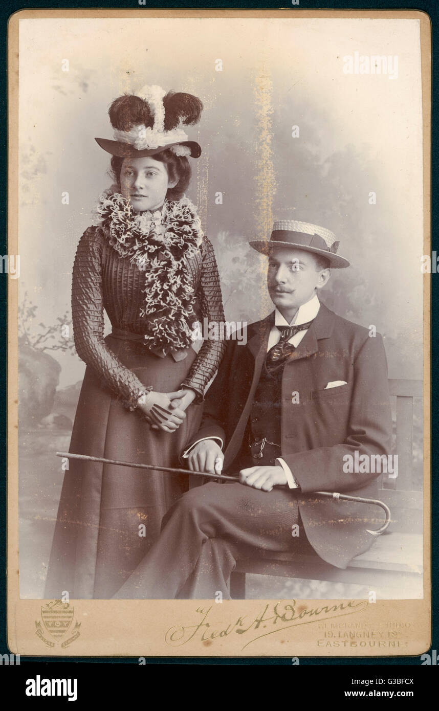 He: straw boater, cane, wing  collar & single-breasted suit.  She: hat adorned with chiffon  & plumes, - Stock Image