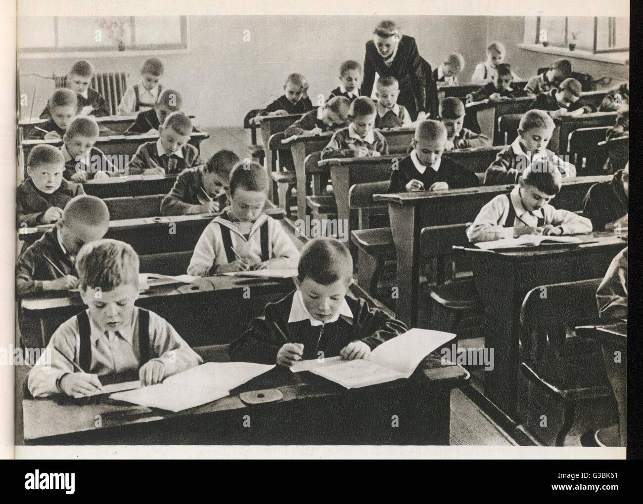Beginning of the term at  School no 170, Sverdlov  district, Moscow.  The teacher  looks at the work of one of  - Stock Image
