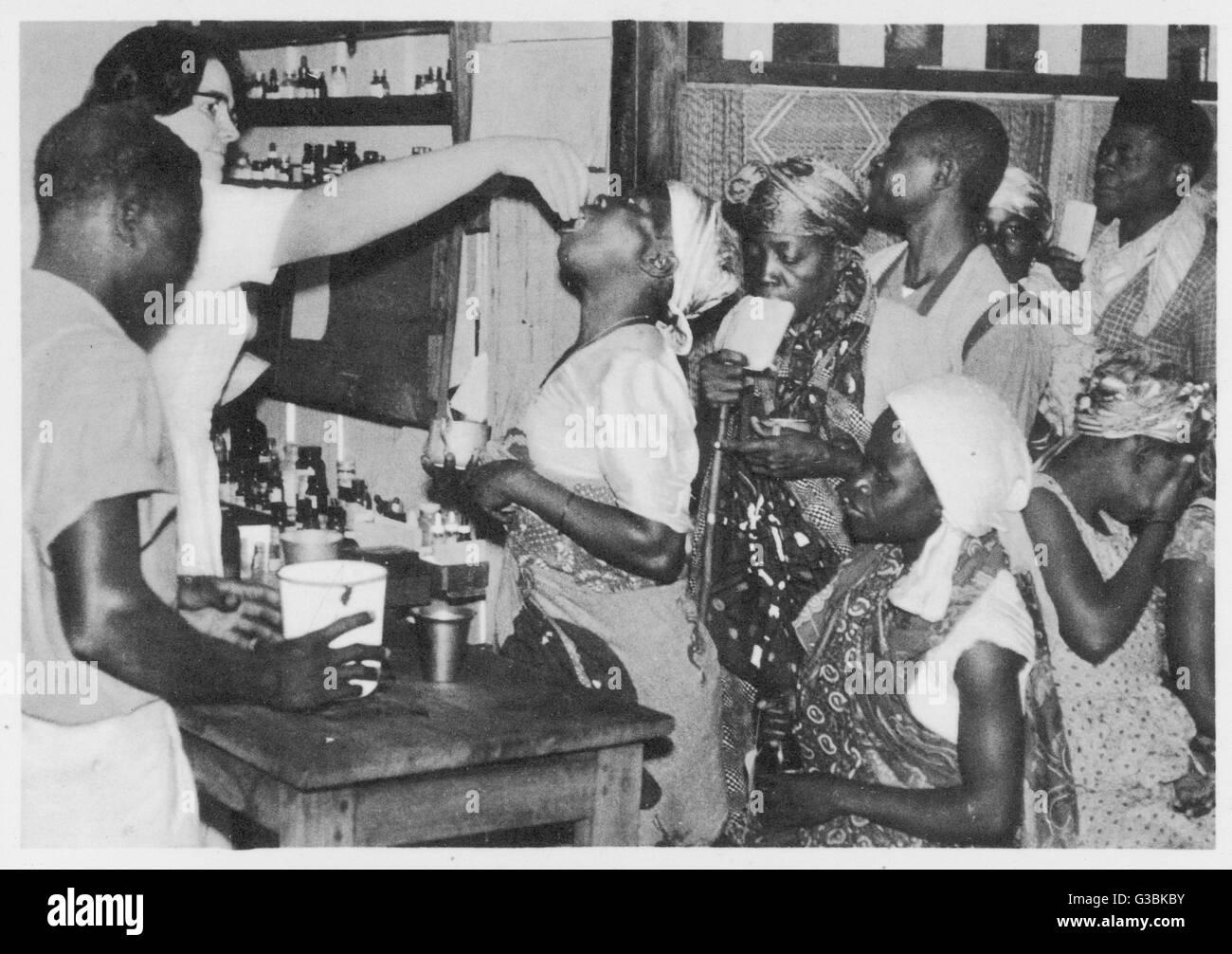 Treating patients at Lambarene, Africa.        Date: 1956 - Stock Image