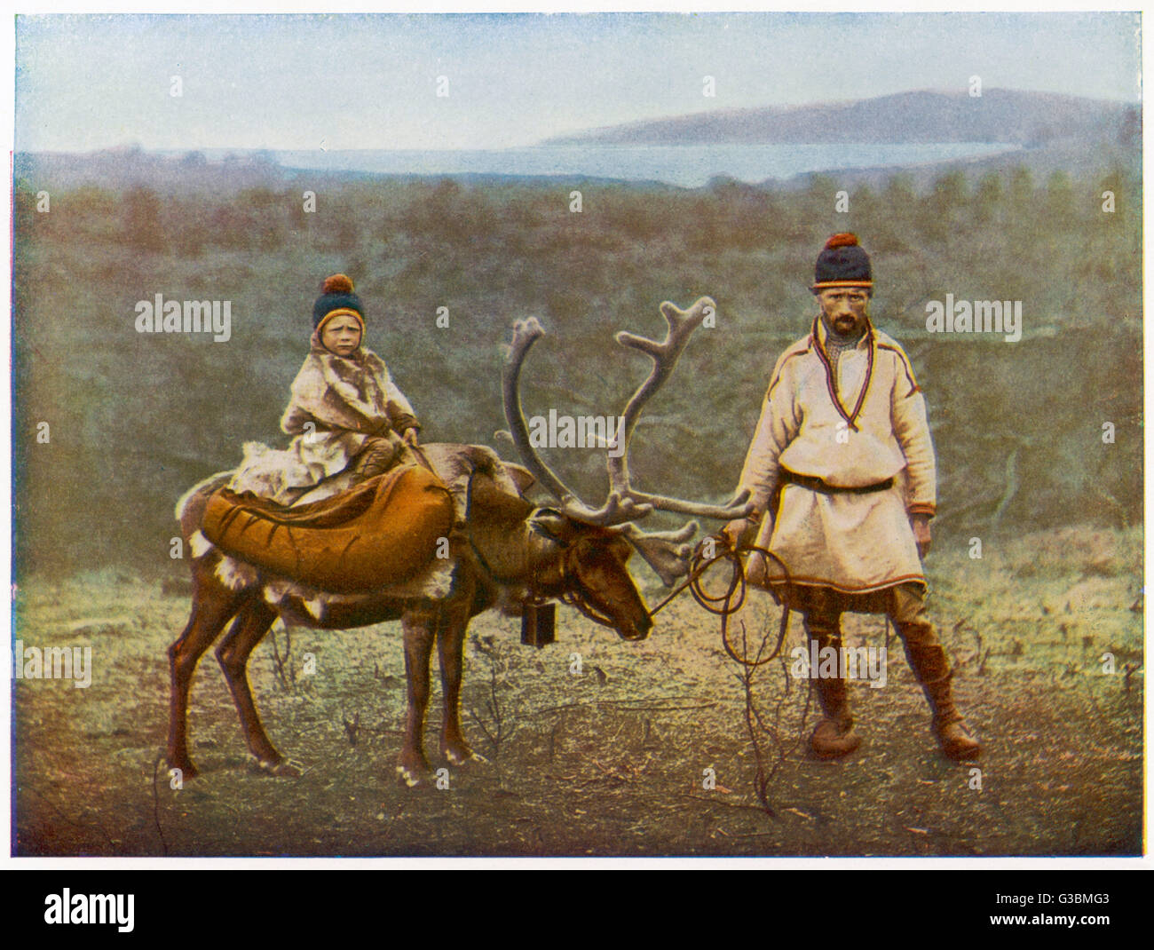 Lapp father and son, with a domesticated reindeer.        Date: 1920s - Stock Image