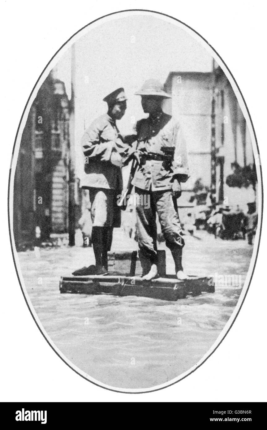 On traffic duty in flooded  Hankow, a Chinese policeman  aided by a soldier, stationed  on an anchored box      - Stock Image