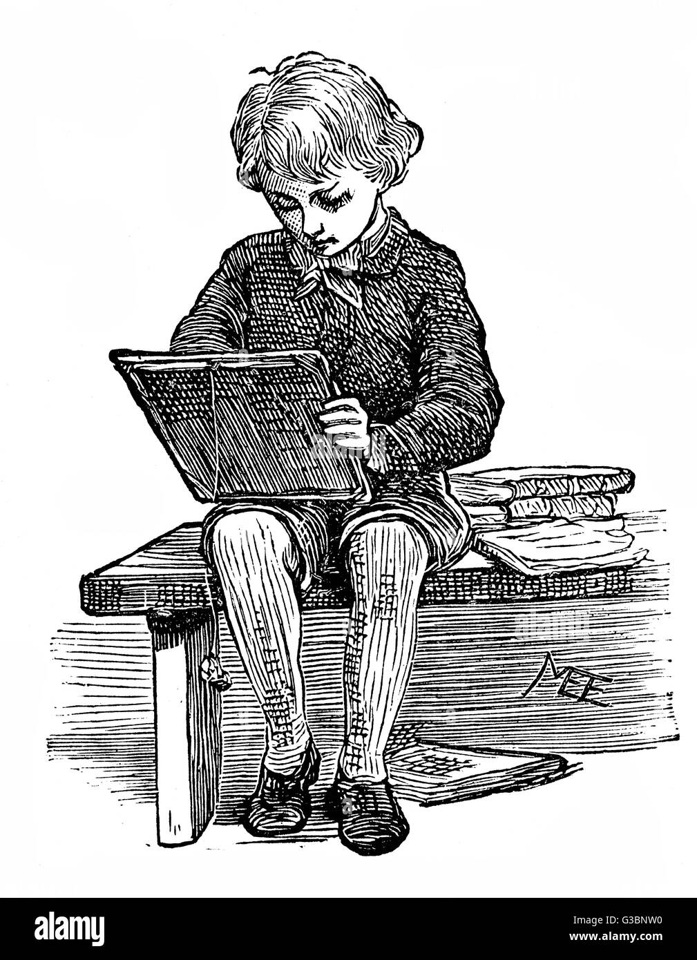 A studious little schoolboy,  sits on a bench surrounded by  books and practices writing on  his slate. A sponge - Stock Image