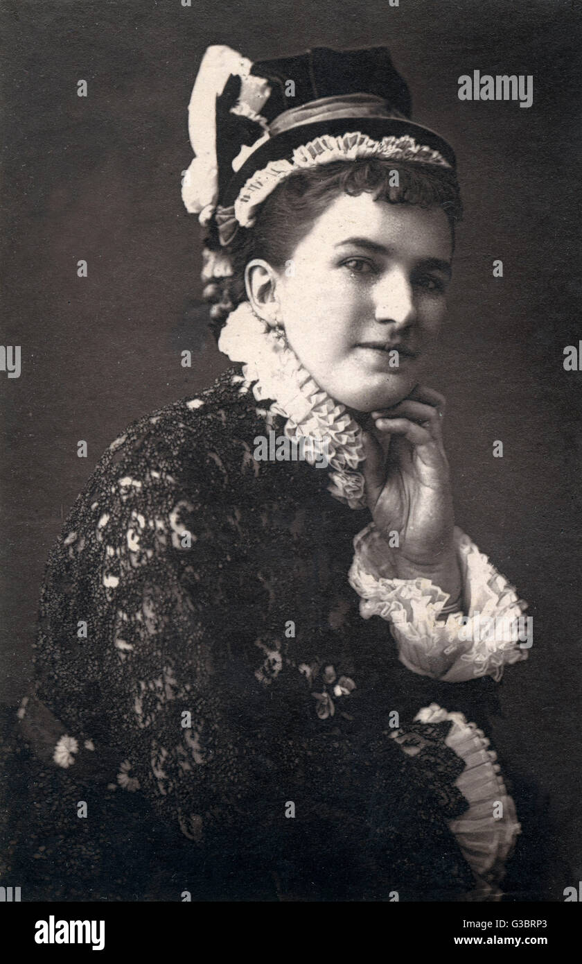 A Victorian woman in a hat and dress with frilly white ruff and cuffs, possibly an actress in theatrical costume. Stock Photo