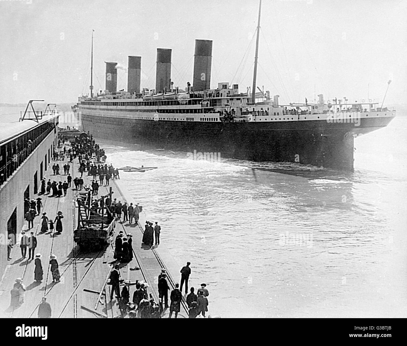 RMS Olympic, White Star Line cruise ship, leaving Southampton, with people watching from the quay.   early 20th - Stock Image
