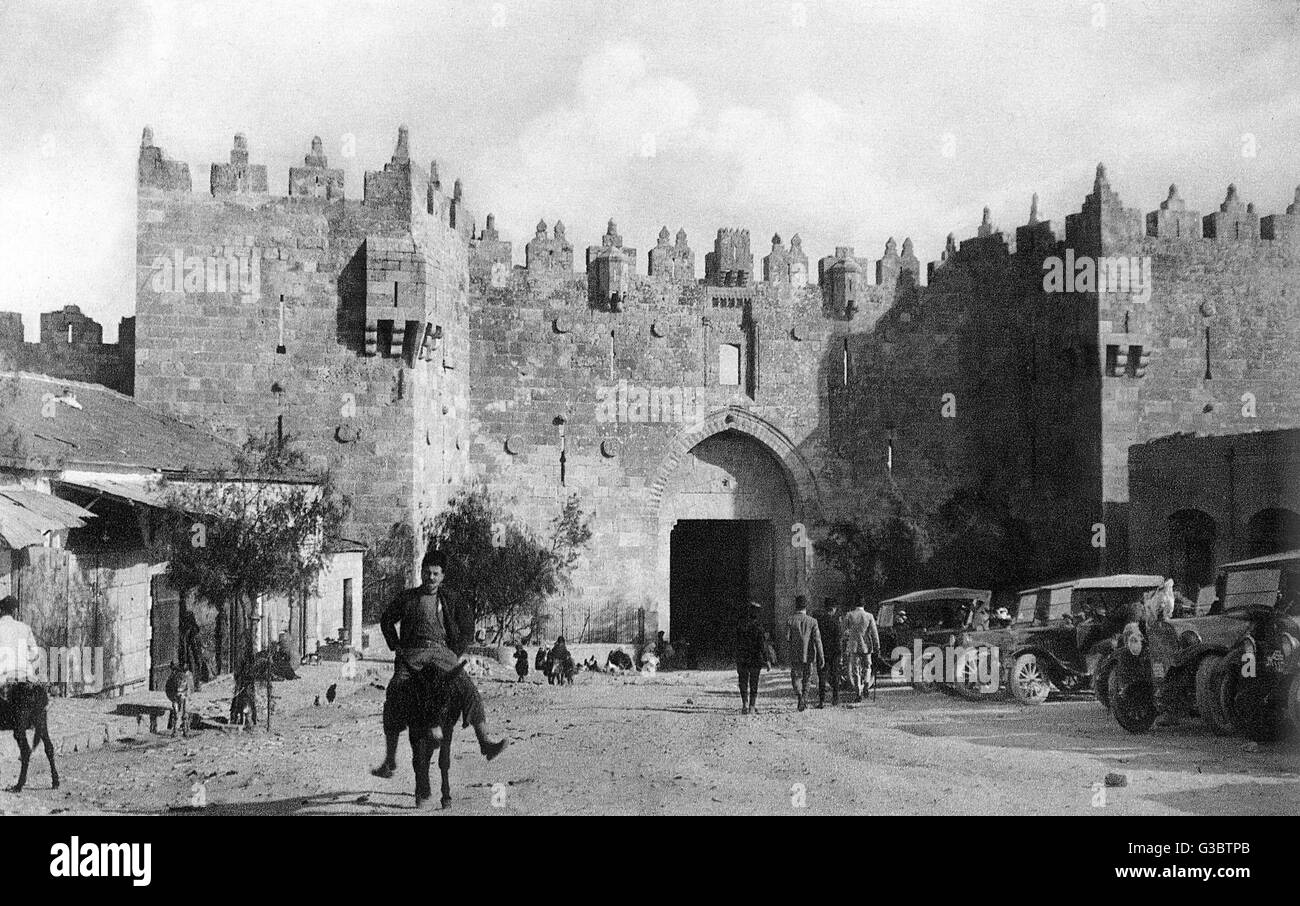 Damascus Gate, Jerusalem, with people and parked cars.      Date: 1920s - Stock Image