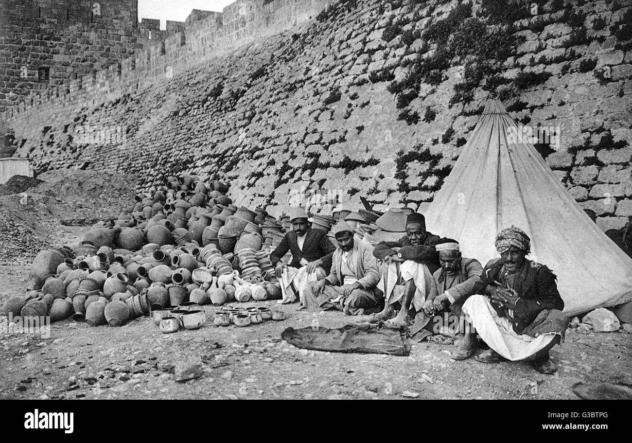 Pottery dealers at the City Wall, Jerusalem.     Date: 1920s - Stock Image