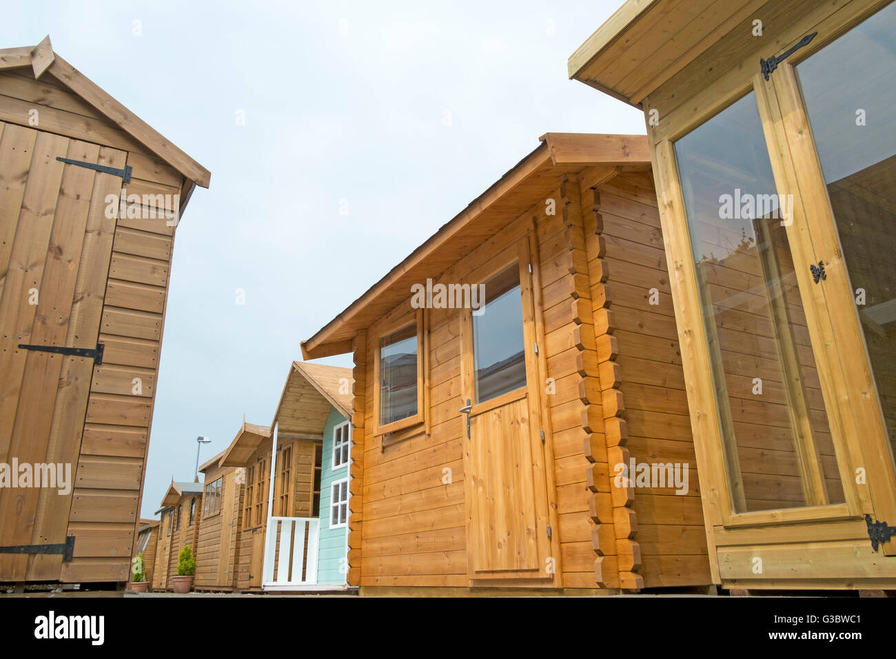 Tanalised timber workshop, home office or wooden summer houses, of log lap construction, storage sheds built of - Stock Image