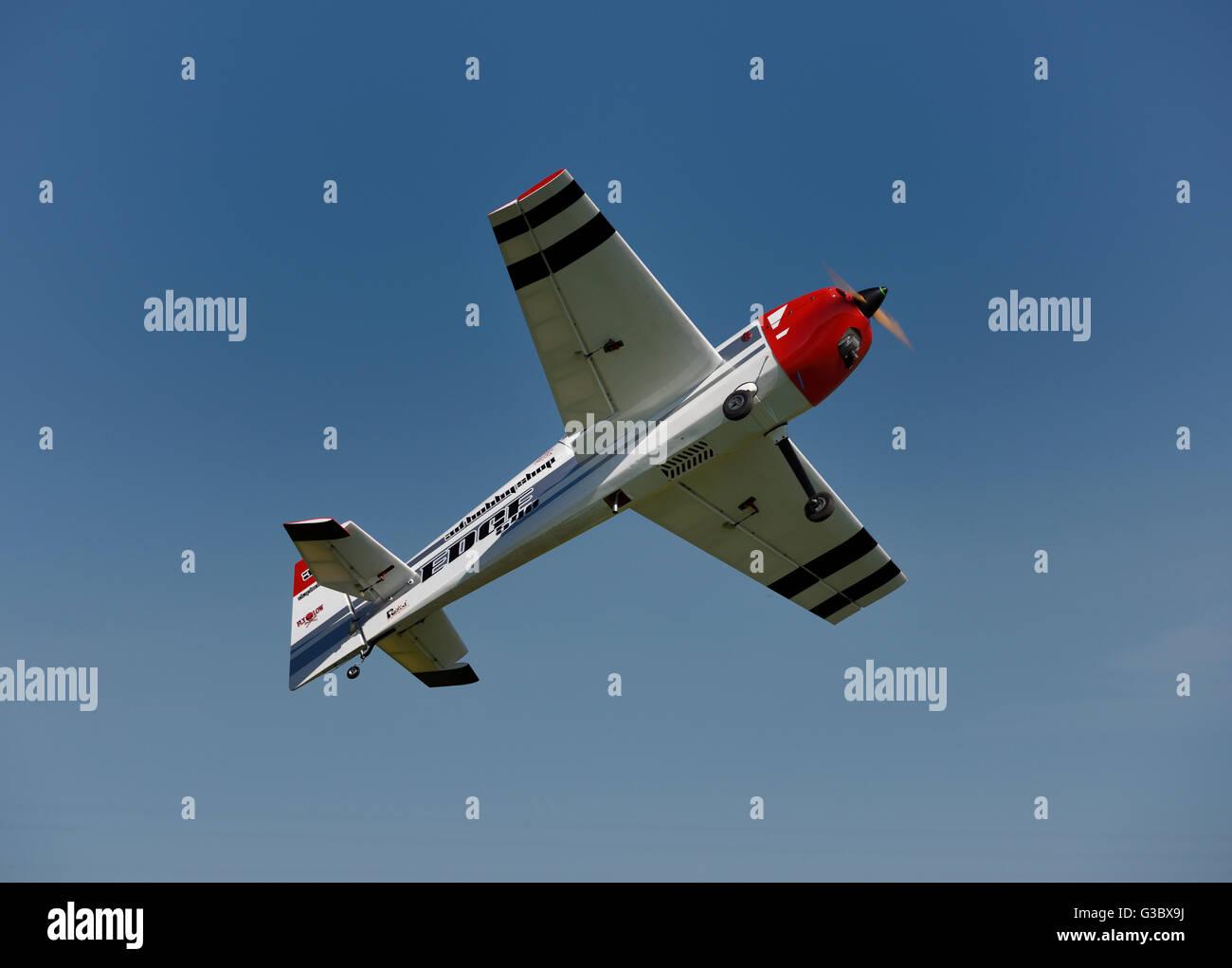 Single prop radio controlled airplane flying overhead - Stock Image