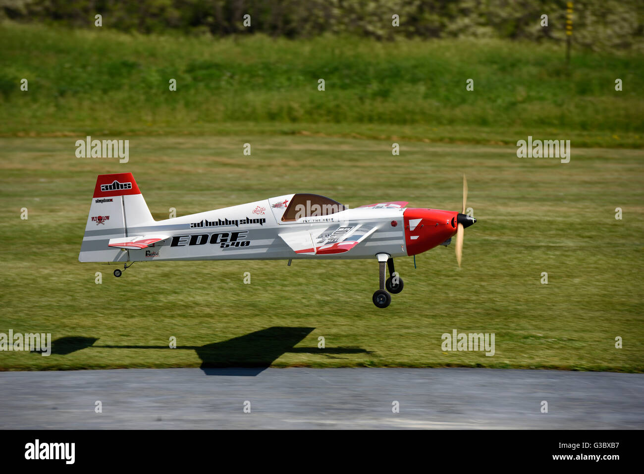 Single Prop gas engine radio controlled airplane landing in a grass field - Stock Image