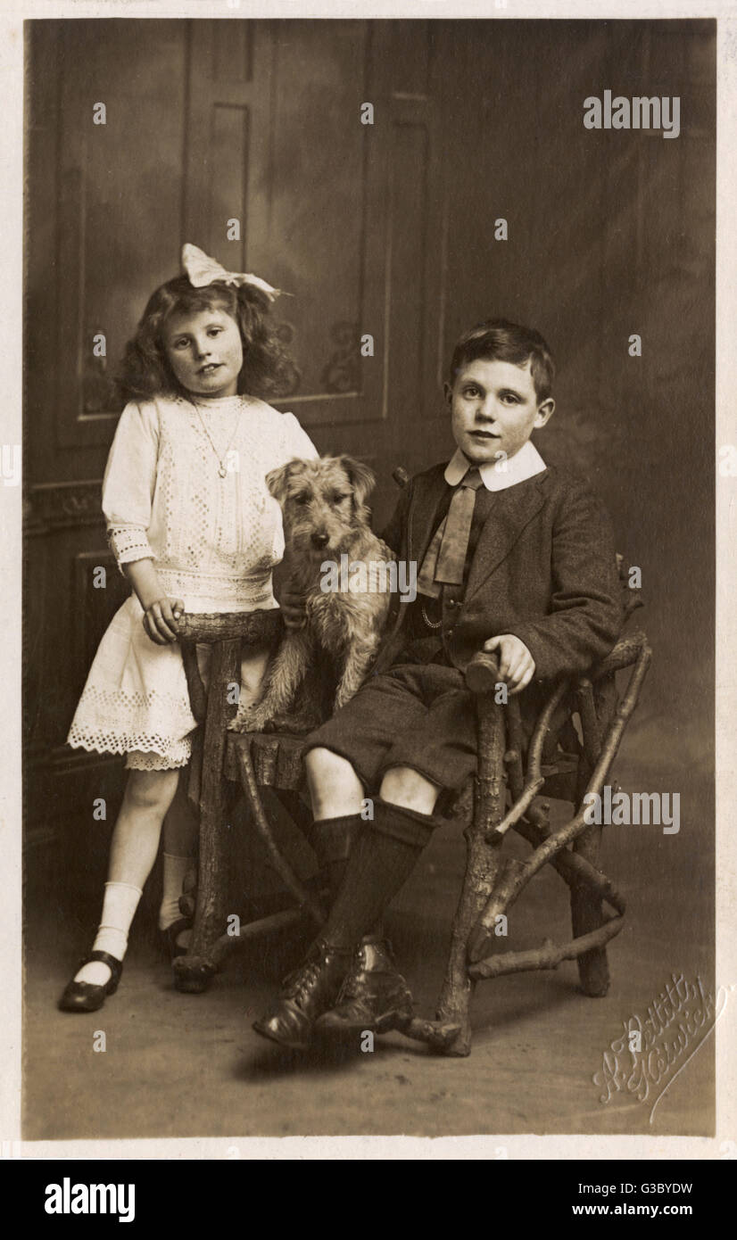 A Brother and Sister pose for a studio portrait photograph with their pet dog.     Date: circa 1909 - Stock Image