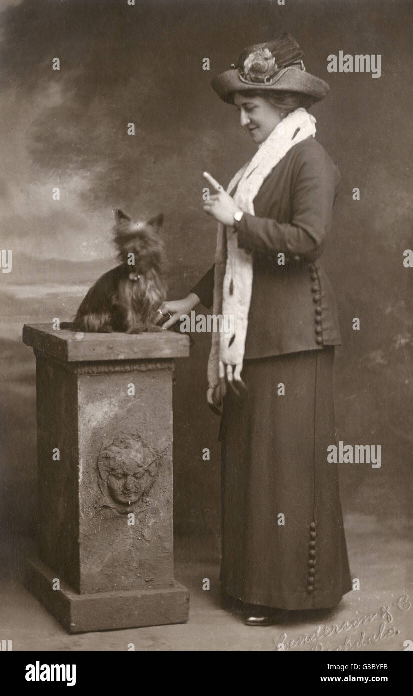 Spontaneous photograph of a woman teaching her dog     Date: early 20th century - Stock Image