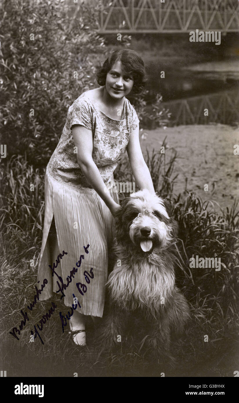 Woman with her friendly Bearded Collie.     Date: 20th century - Stock Image