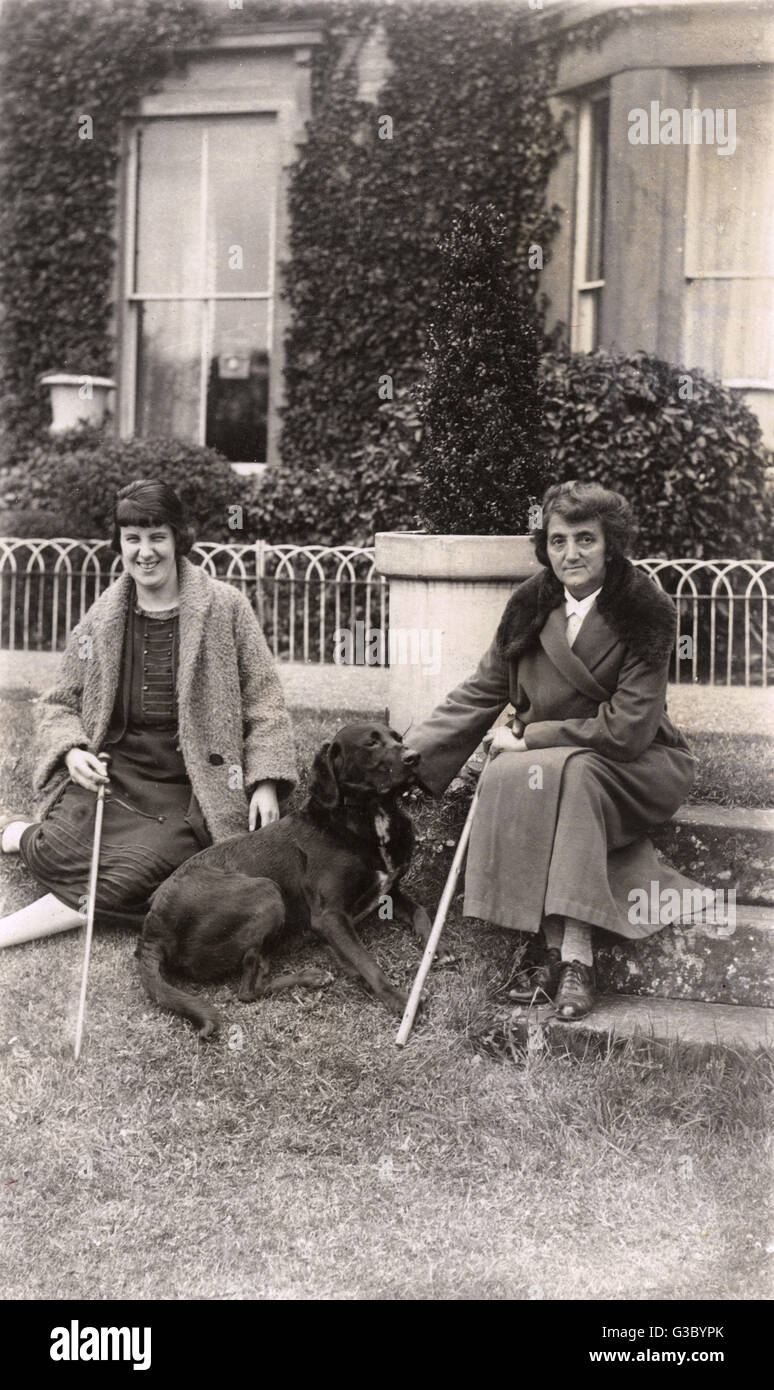 Women with a mongrel in the garden.     Date: 20th century - Stock Image