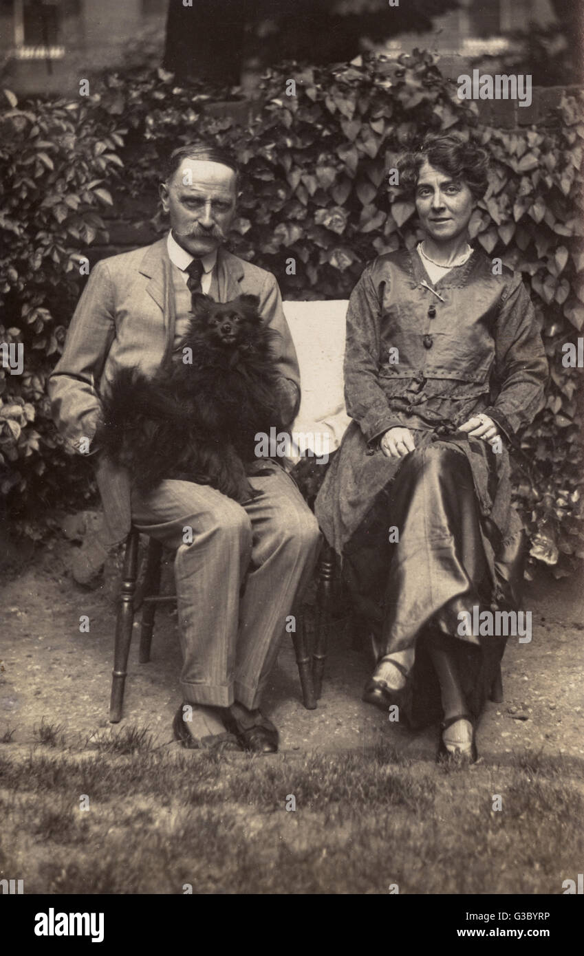 Couple with Pomeranian in the garden.     Date: 20th century - Stock Image