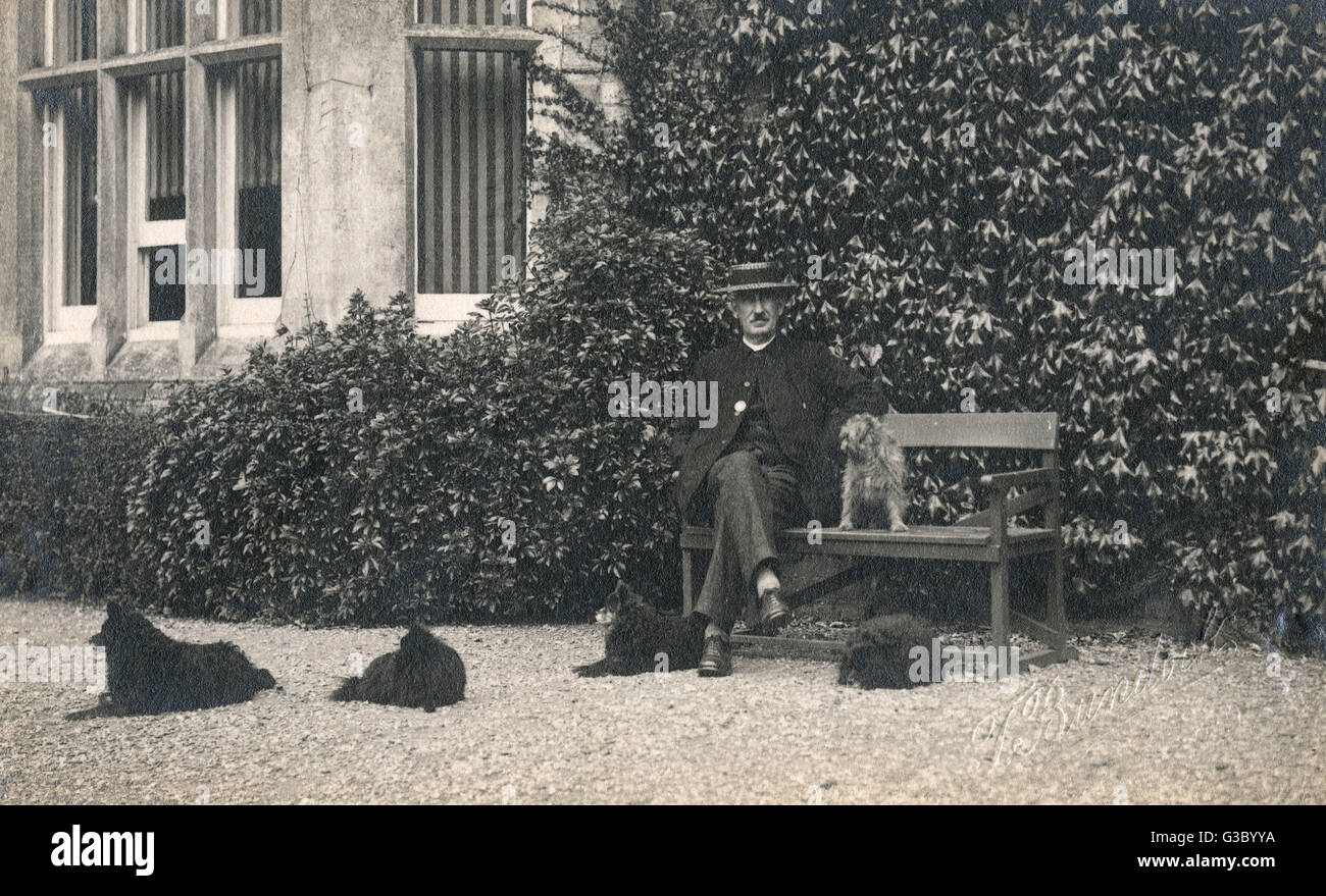 A middle aged man in a straw boater sitting on a bench with one dog on the bench with him, and four small black - Stock Image