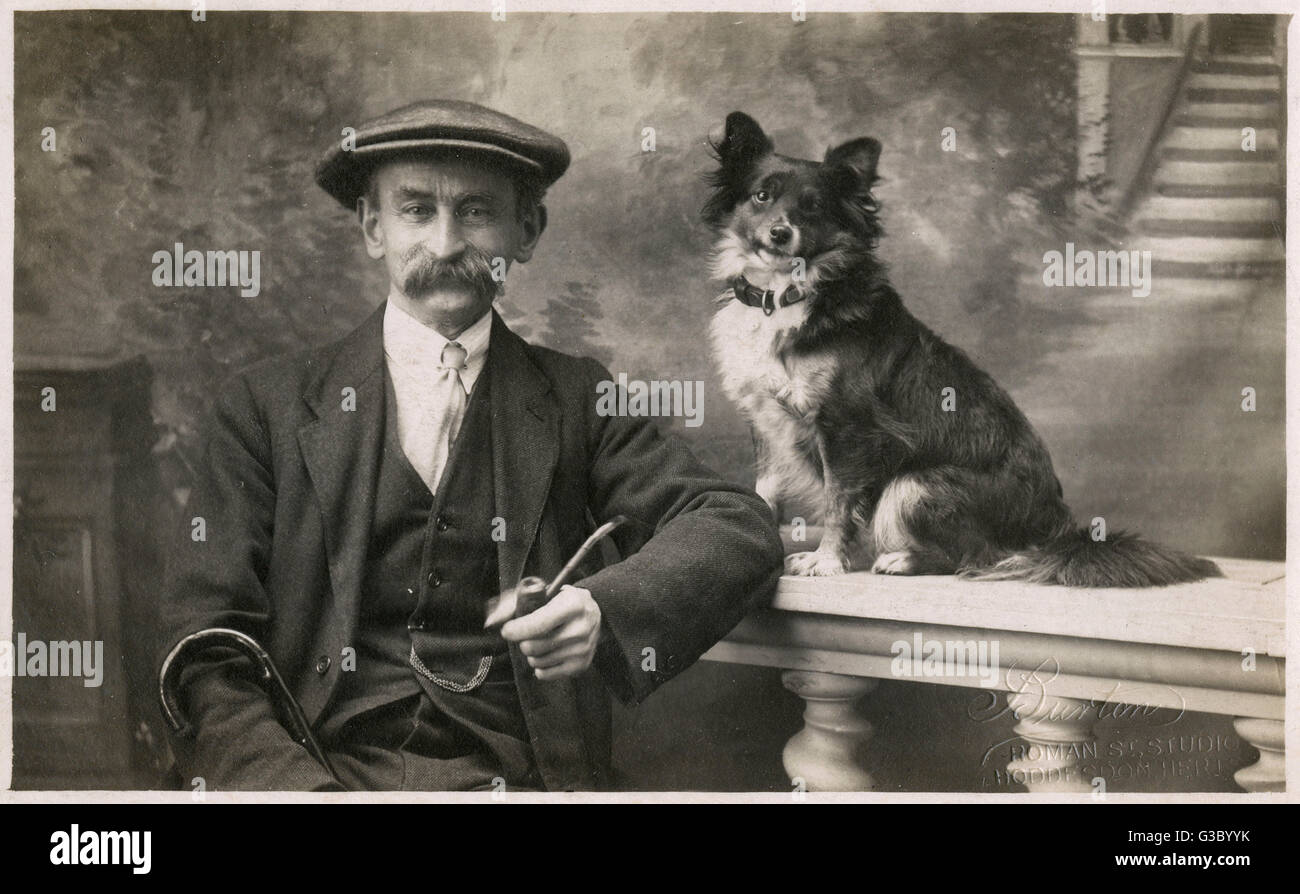 Man with his pet dog in a studio photo, sent as a Christmas greetings card on 24 December 1923.      Date: 1923 - Stock Image