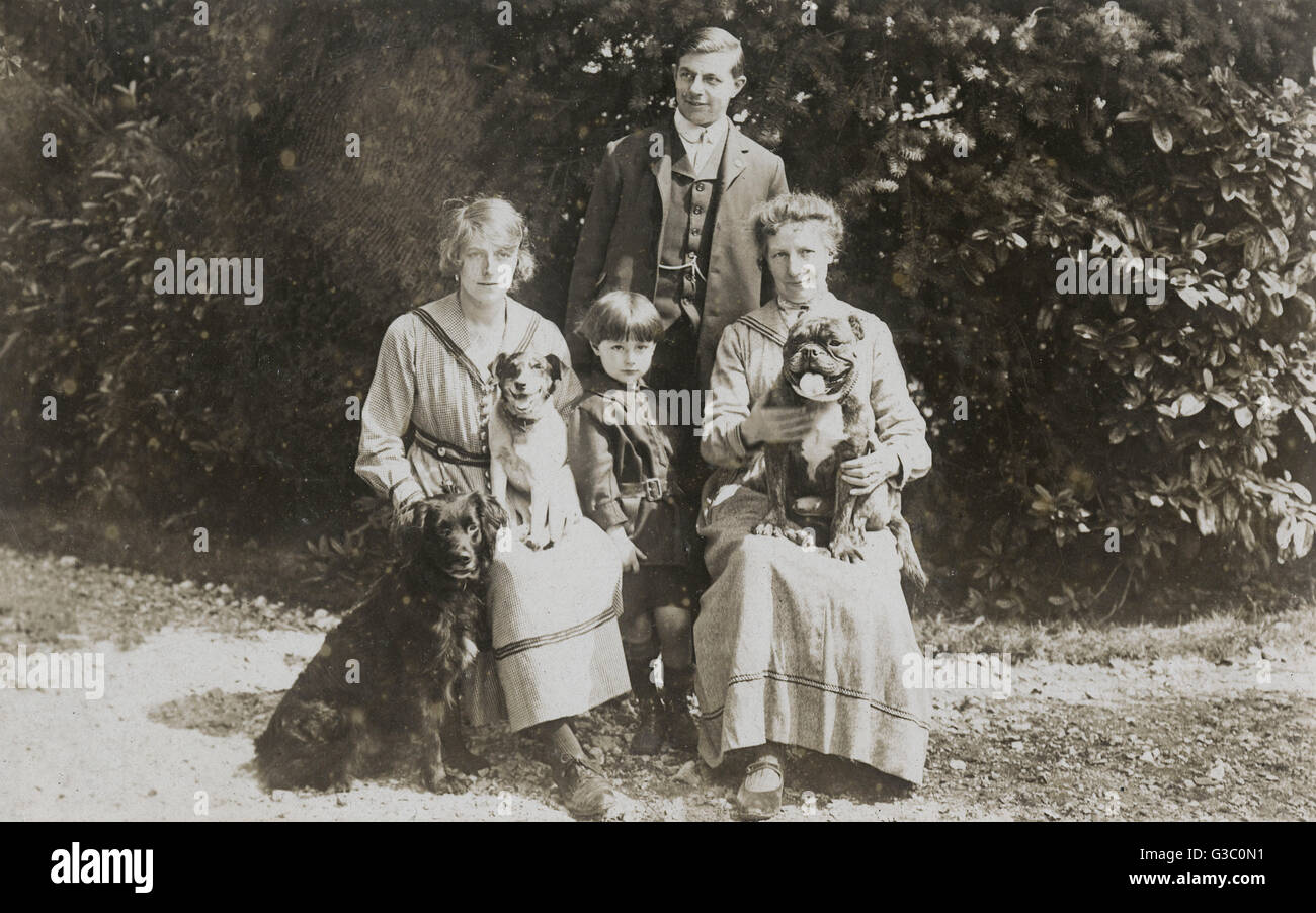 Four people and three dogs in a garden.      Date: circa 1920s - Stock Image