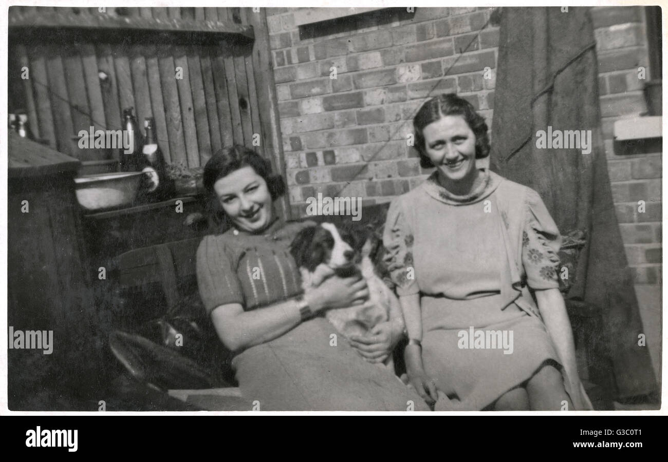 Two women with a dog in a back garden, dated August 1931.      Date: 1931 - Stock Image