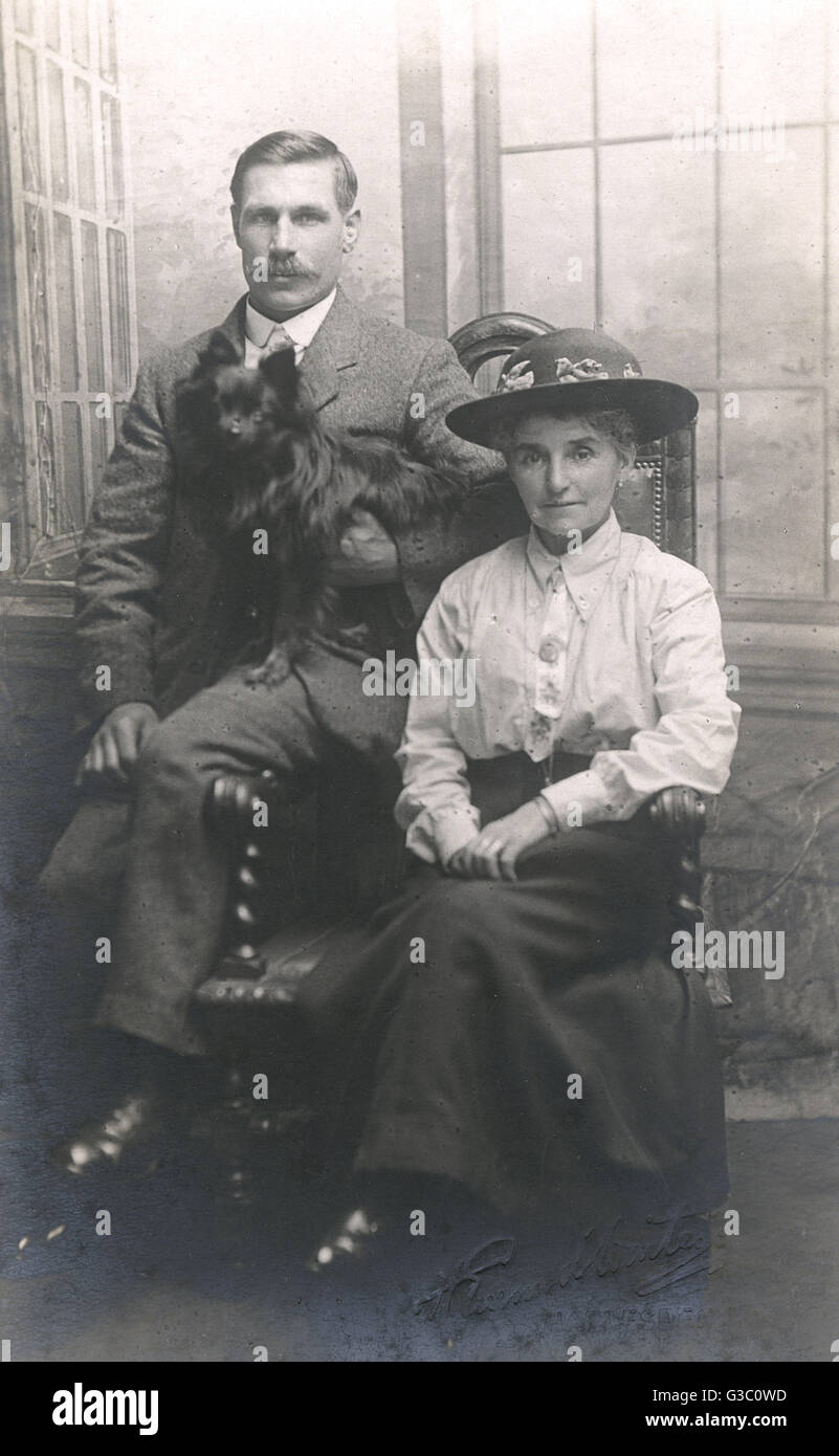 Studio portrait, couple with a small black lapdog, photo by Everard Winter of Harlesden, NW London.      Date: circa - Stock Image