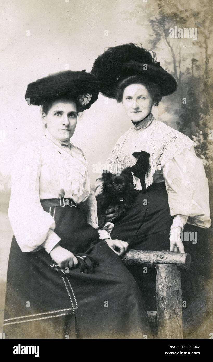 Studio portrait, two women with a small black dog.      Date: 1900s - Stock Image