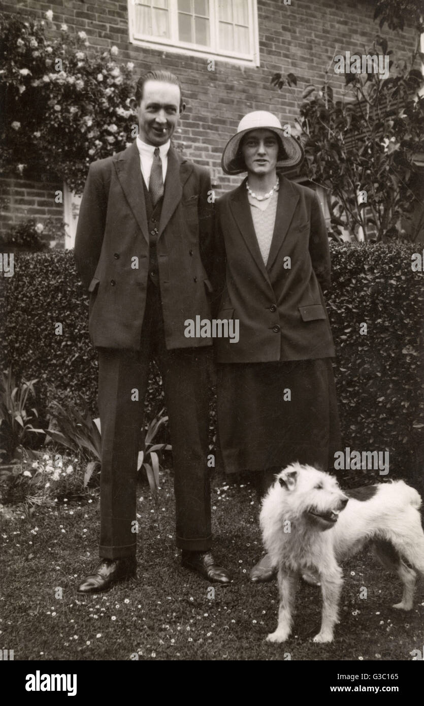 Man and woman with a terrier dog in a garden.      Date: circa 1930s - Stock Image
