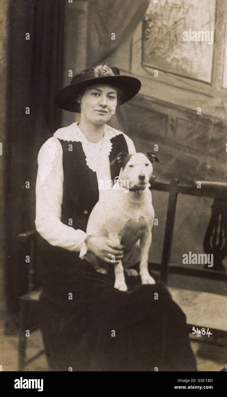 Studio portrait, young woman with a plump bull terrier on her lap.      Date: circa 1920s - Stock Image