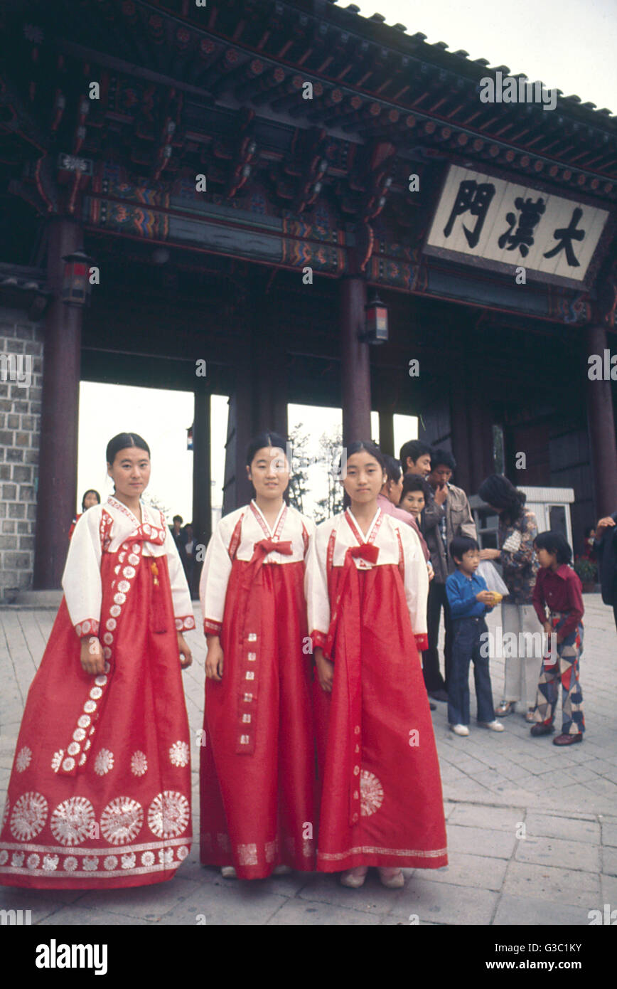 Visitors in national dress outside the gate of Deoksu (Deoksugung, Duksoo) Palace, Seoul, South Korea.      Date: Stock Photo