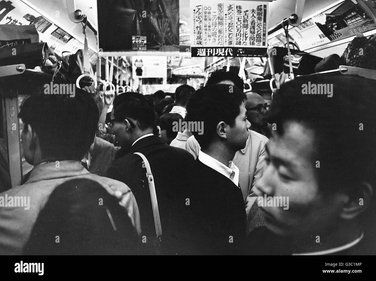 People in a packed train during the evening rush hour, Tokyo, Japan.      Date: circa 1960s - Stock Image