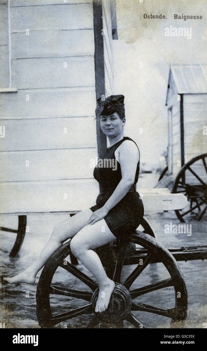 Lady Bather at Ostende, Belgium sat on the wheel of a bathing machine. Her costume is possibly rather daring for - Stock Image